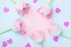 Модель-макет дня рождения или свадьбы с розовыми бумажными списком, сердцами и тюльпаном цветет на голубом взгляд сверху предпосы Стоковая Фотография RF