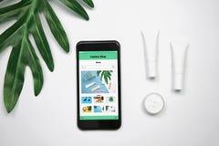Модель-макет косметической cream бутылки, пустой пакет ярлыка и smartphone показывают ходить по магазинам применения экрана онлай Стоковые Изображения RF