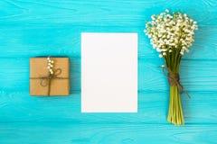 Модель-макет с букетом ландыша цветков и пустого бумажного листа на голубом деревянном столе, взгляд сверху подарочной коробки, Стоковое Фото