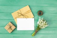 Модель-макет с букетом ландыша цветков и пустого бумажного листа на голубом деревянном столе, взгляд сверху подарочной коробки, Стоковая Фотография RF