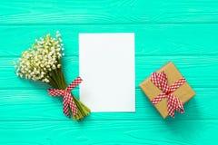 Модель-макет с букетом ландыша цветков и пустого бумажного листа на голубом деревянном столе, взгляд сверху подарочной коробки, Стоковая Фотография