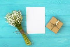 Модель-макет с букетом ландыша цветков и пустого бумажного листа на голубом деревянном столе, взгляд сверху подарочной коробки, Стоковые Изображения