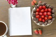Модель-макет с пустыми блокнотом, чашкой кофе и тортом роза букета малая Хлебопекарня frash клубники и шоколада Стоковое Изображение