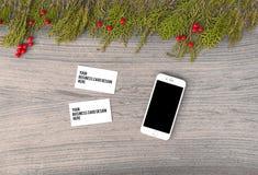Модель-макет martphone визитных карточек на время рождества ветви и украшения ели на деревянной предпосылке Плоское взгляд сверху Стоковое Изображение RF