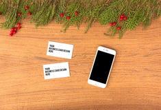 Модель-макет smartphone визитных карточек на время рождества ветви и украшения ели на деревянной предпосылке Плоское взгляд сверх Стоковое Изображение RF