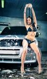 Модель на мытье автомобиля в гараже. Стоковые Изображения