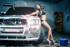 Модель на мытье автомобиля в гараже. Стоковое Изображение