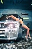 Модель на мытье автомобиля в гараже. Стоковые Фото