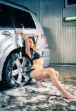 Модель на мытье автомобиля в гараже. Стоковое Фото