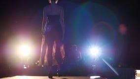 Модель подиума в высокие пятки в платья идет на подиум в освещении прожектора перед публикой сток-видео
