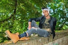 Модель сумасбродного битника мужская с стеклами, сорванными джинсами, ботинками зимы и белым шарфом Модельный идти через булыжник стоковая фотография