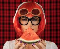 Модная женщина в красном парике и стеклах, слушая к музыке в белых наушниках и держа часть зрелого Стоковое Изображение