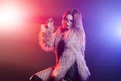 Модная молодая женщина в пушистом розовом пальто, неоновое свето Портрет красивой ультрамодной девушки Стоковое Изображение
