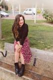 Модная молодая и жизнерадостная женщина сидя на стенде смеясь застенчиво стоковое фото