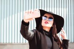 Модно одетая женщина носит шляпу и солнечные очки, принимая собственную личность стоковое изображение rf