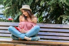 Модно одетая молодая женщина на улице на солнечном вечере Девушка в джинсах, блузке и небольшой шляпе сидит на стенде и стоковые фото