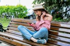 Модно одетая молодая женщина на улице на солнечном вечере Девушка в джинсах, блузке и небольшой шляпе сидит на стенде и стоковые фотографии rf