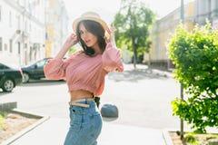 Модно одетая молодая женщина на улице на солнечном вечере Красивая девушка в джинсах и небольшой шляпе стоящ и смотрящ стоковая фотография rf