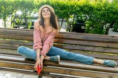 Модно одетая молодая женщина на улице на солнечном вечере Красивая девушка в джинсах, блузке и небольшой шляпе сидит на a стоковое фото