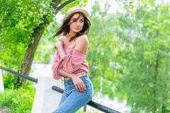 Модно одетая молодая женщина на улице на солнечном вечере Красивая девушка в джинсах и небольшой шляпе стоит и смотрит стоковая фотография