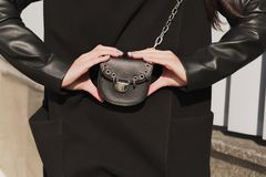 Модно одетая молодая модель в черном пальто держа малое blac стоковая фотография
