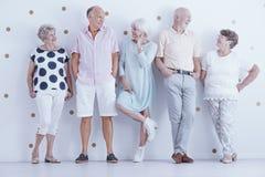 Модно одетые усмехаясь старшие люди представляя в ярком studi стоковое фото