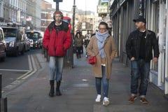 Модно одетые человек и женщина пересекают дорогу около Ковент Гардена на солнечный день стоковая фотография