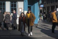 Модно одетые человек и женщина пересекают дорогу около Ковент Гардена на солнечный день стоковое изображение