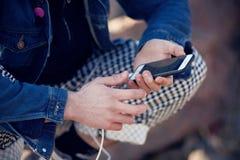 Модно одетый подросток держа телефон касания стоковое фото