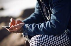 Модно одетый человек держит телефон касания стоковые изображения