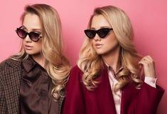 Модные 2 белокурых женщины в пальто с солнечными очками Фото зимы осени моды Стоковое фото RF