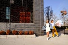 Модные городские девушки нося ультрамодное обмундирование при воздушные шары идя на улицу Нью-Йорка Стоковая Фотография RF