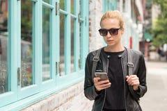 Модные молодая женщина в черной кожаной куртке и занятый с ее мобильным телефоном пока идущ улица города Стоковые Изображения