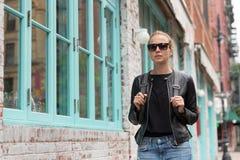 Модные молодая женщина в черной кожаной куртке и занятый с ее мобильным телефоном пока идущ улица города Стоковая Фотография RF