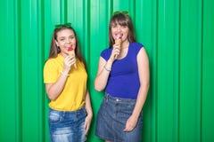 Модные молодые женщины с конусом мороженого на зеленой стене стоковые изображения