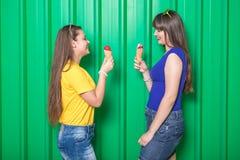 Модные молодые женщины с конусом мороженого на зеленой стене стоковое изображение
