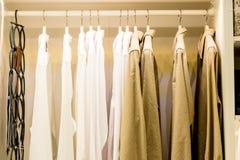 Модные одежды вися на шкафе на современной уборной тонизированное изображение Шкаф вполне много блузок на вешалках в стоковое фото rf