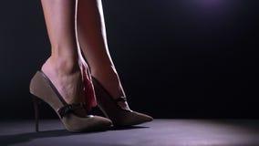 Модные пятки девушки конца-вверх носят ботинок с пяткой в черной темной студии сфокусировали акции видеоматериалы