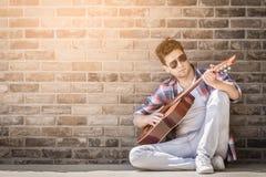 Модный акустический гитарист сидя на земле и полагаться стоковое фото rf