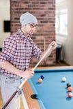 Модный игрок снукера обтирает сигнал с мелом готовым для начала игры стоковая фотография