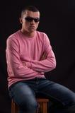 Модный молодой парень в солнечных очках сидя в стуле стоковое фото rf