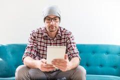 Модный молодой человек используя прибор планшета пока сидящ на его оф стоковые фотографии rf