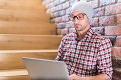 Модный фрилансер сидя на лестницах в офисном здании с руками на клавиа стоковое фото