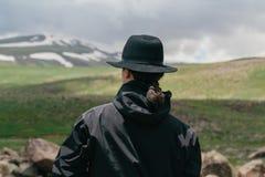 Модный человек в шляпе на фоне армянских гор стоковые фото