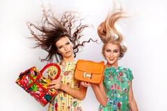 2 модных блестящих девушки с кожаными сумками Изолят стоковое фото