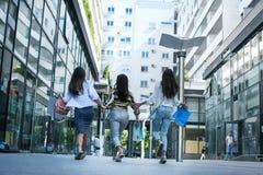 3 модных молодой женщины гуляя с хозяйственными сумками от стоковые фотографии rf