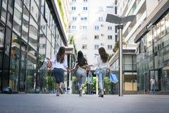 3 модных молодой женщины гуляя с хозяйственными сумками от стоковое фото rf