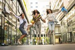 3 модных молодой женщины гуляя с хозяйственными сумками Sati стоковые изображения