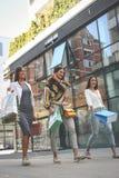 3 модных молодой женщины гуляя с хозяйственными сумками Wome стоковые изображения rf