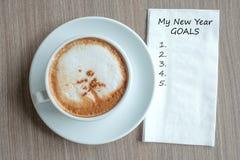 МОЕ слово ЦЕЛЕЙ НОВОГО ГОДА с горячей кофейной чашкой капучино на предпосылке таблицы на утре Начало Нового Года новое, разрешени стоковая фотография rf